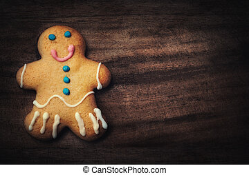 Christmas homemade gingerbread man cookie on wooden table. Christmas Holiday Background.