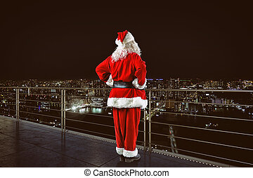 Christmas is coming. Santa Claus on a roof view city