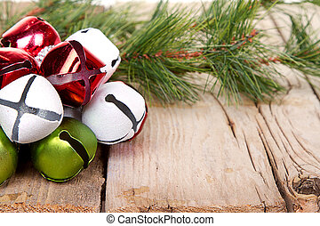 Christmas Jingle bells and a pine branch on a rustic wooden ...