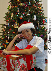 I cute young girl in a Santa hat, sitting in front of a Christmas tree, holding a large gift.