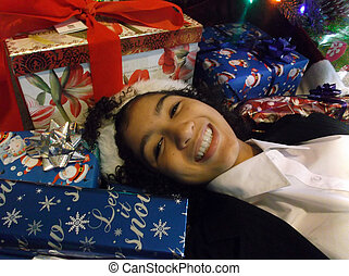 A cute tan girl lies in a pile a wrapped Christmas gifts.