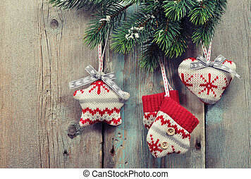 Christmas knitted decoration on fir tree branches on wooden...