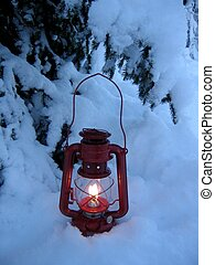 christmas lamp - Red lamp shining in the snow under a spruce...