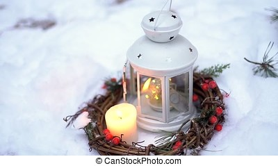 Christmas lantern with candle. It stands in the snow.