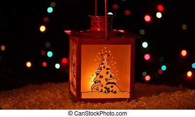 Christmas lantern with candle shining in the darkness, on the background of garlands, looping