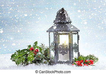 Christmas lantern with Holly leaves and berries on a snowy background.