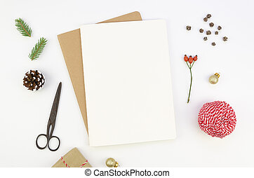 Christmas letter writing on a blank paper on white background with xmas decorations. Top view mockup
