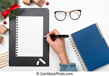 Christmas letter writing on paper on white desk with decorations. Wish list writing. 2020 resolution list