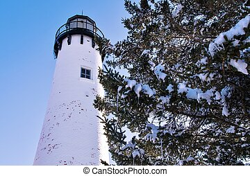 Historic Point Iroquois Lighthouse framed by pine boughs with fresh fallen snow and icicles. The lighthouse is on Whitefish Bay Scenic Byway located in Hiawatha National Forest. Brimley, Michigan.