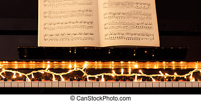 Christmas lights and score on a piano keyboard, front view