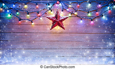 Christmas Lights And Star Hanging On Snowy Plank