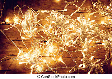 Christmas lights over wooden background. Festive lights,...