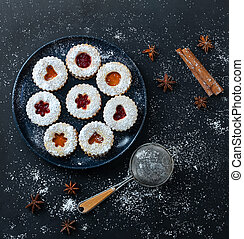 Homemade Christmas Linzer cookies with apricot and strawberry jam on dark background. Top view. Flat lay.