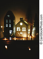 Christmas little houses with lights and christmas trees in night. Miniature house among trees in christmas evening. Stylish festive decorations. Winter wonderland. Merry Christmas and New Year
