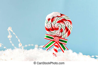 Christmas Lollipop in the snow on a blue background. Happy New year concept. Christmas background. Copy space.