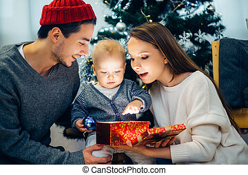 Christmas magic gift box and happy parents and Child baby