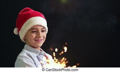 Christmas Magic - Happy lad in Santa hat creating the...