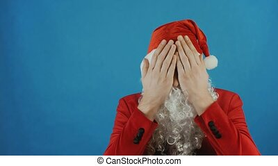 Christmas, man like a Santa covers his eyes by palms of hands, New year 2019, blue background