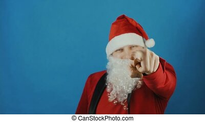 Christmas, man like a Santa shows index finger into the camera, New year, on blue background