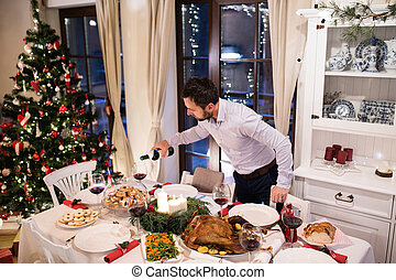Christmas meal laid on table. Man pouring wine into glasses.