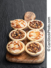 Christmas mini mince pie on wooden board on black stone background
