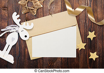 Christmas mockup envelope with blank paper on brown wooden background. Letter to Santa Claus. Christmas winter setting - star, elk, ribbon