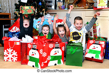 Four children sit surrounded by Christmas packages. It is Christmas morning and their excitement is overflowing. There are two girls and two boys and they scream with joy.