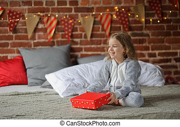 Little girl rejoices to the Christmas gift.