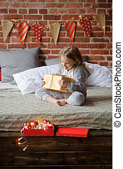Little girl rejoices to the Christmas gift