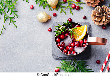 Christmas Moscow mule, holiday drink in a copper mug on a grey stone background. Top view. Copy space.