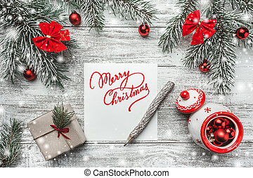 Christmas motivational theme, of a notepad and vintage pencil, with space for text, with red bow, fir, present boxes, globes, handmade toys on wooden background, view from above, greeting card