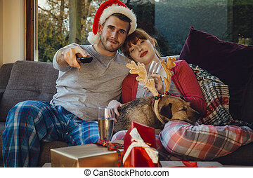 Christmas Movie Night - Young couple at home with their pet...