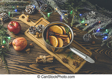 Christmas mulled red wine with the addition of spices and citrus fruits in a small metal pan on a rustic wooden table, top view. Pot of mulled wine, traditional christmas drink.