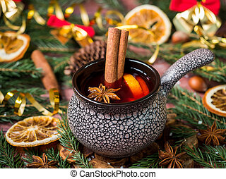 Christmas mulled wine with cinnamon, orange and star anise in a ceramic bowl with winter decorations