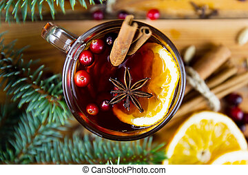 Christmas mulled wine with cinnamon, spices and orange slices on a wooden background. Winter hot drink