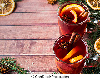 Christmas mulled wine with orange and spices on wooden background. Copy space