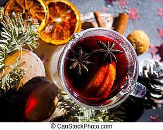 Christmas mulled wine with spices in glasswith plaid and snow on a christmas tree on dark background, The glass cup of hot winter drink