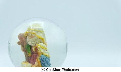Christmas nativity scene inside glass ball on white background.