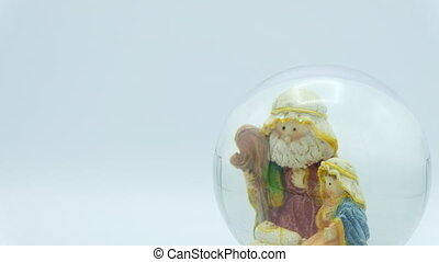 Christmas nativity scene inside glass ball on white background. Left copy space.