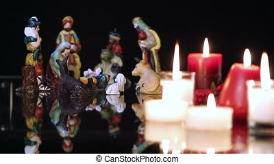 Christmas nativity scene with candles on black background....