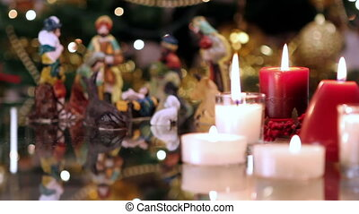 Christmas nativity scene with candles in front of Christmas...