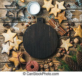 Christmas, New Year background. Gingerbread cookies, sugar powder, nuts, spices, baking molds, fir-tree branch, pine cones on rustic background, dark round wooden board in center, top view, copy space