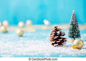 Christmas, New Year decoration, cone, ball, tree with snow on blue background. Copy space.