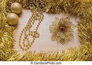 Christmas New Year holiday background. Golden tinsel, flower, garland and balls om wooden background