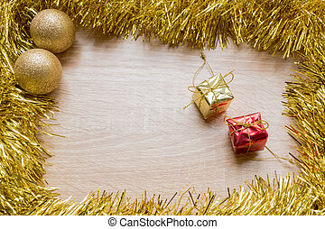 Christmas New Year holiday background. Golden tinsel, gift, and balls on wooden background
