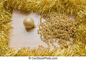 Christmas New Year holiday background. Golden tinsel, sparkle ball and garland on wooden background