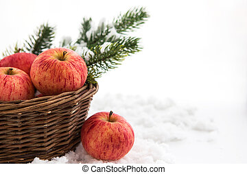 Christmas ?omposition with red apples in basket and branch of c