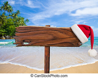 Christmas on beach concept. Wooden signboard with Santa's hat.