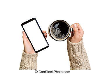 Christmas online shopping. female hands in sweater Touch screen mobile phone with cup of coffee. Woman typing on mobile phone isolated on white background