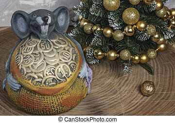 Christmas or New Year composition. Christmas tree with festive decor and the symbol of 2020 a gray rat with coins on a wooden table.
